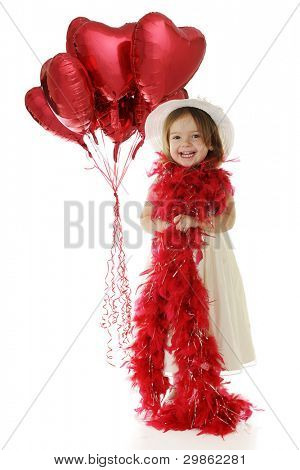 A beautiful preschooler dressed in white and wrapped with a bright red boat.  A bouquet of red heart balloons float behind her.  On a white background.