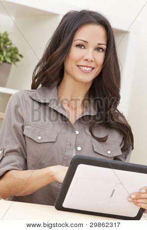 Beautiful, smiling, young brunette woman at home at a table using her tablet computer