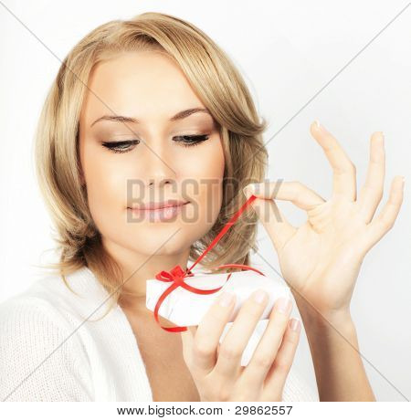 Beautiful female opening gift, closeup woman portrait isolated on white background, pretty blond girl with present box, people celebrating holidays concept
