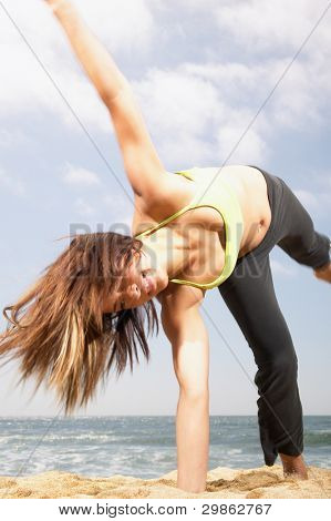 Woman doing cartwheel at beach