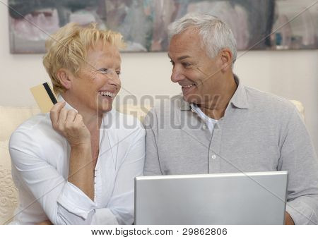 Portrait of an happy aged couple shopping on line using laptop