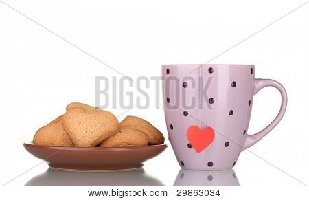 Pink cup with tea bag and heart-shaped cookies on brown plate isolated on white