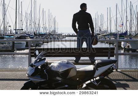 Young man standing on a pier bench