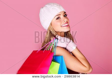 Happy Young Shopper. Pretty smiling girl in winter cap with colorful shopping bags over her shoulder