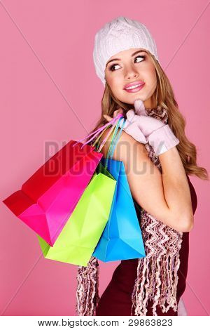Colorful Winter Shopping. Beautiful woman wearing winter accessories carrying three colorful carrier bags over her shoulder