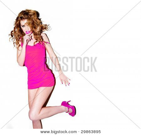 Sexy woman with lovely long wavy auburn hair wearing a very skimpy pink mini dress, studio portrait on white