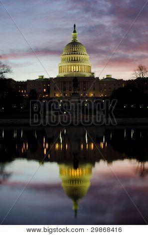 United States Capitol building with mirror reflection at sunrise - Washington DC