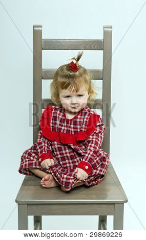 Cute Little Girl In Red Dress Sitting On A Chair