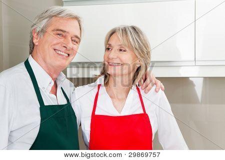 Happy senior Couple mit Schürzen stehen in der Küche