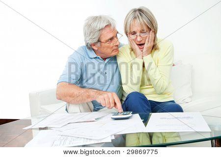 Preocupado casal senior sentado com contas e calculadora em casa