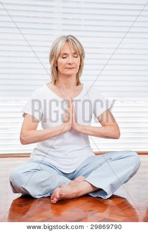 Relaxed senior woman meditating at home on floor
