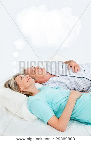 Senior woman with thought bubble in bed with man