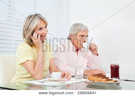 Senior woman using her cell phone at breakfast table