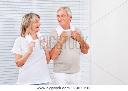 Happy senior couple exercising in fitness center