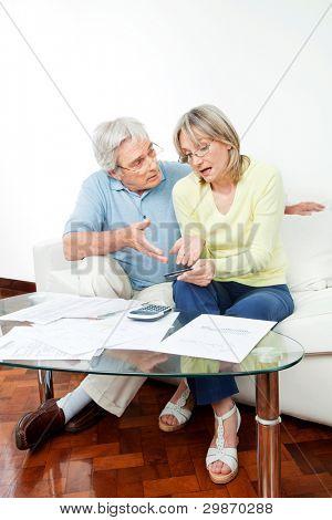Pareja Senior con papeleo peleando por dinero en casa