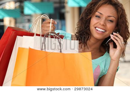 Woman with her shopping bags and talking on her phone