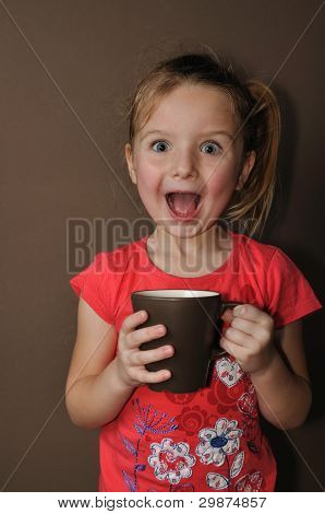 Suprised girl with brown cup