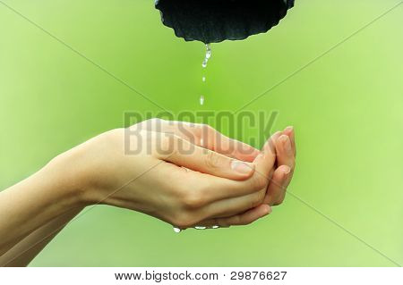 Hands catching clean falling water