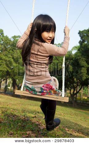 little girl on the swing green sky