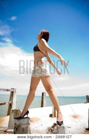 Woman Looks Out To Bright Blue Sky By The Sea