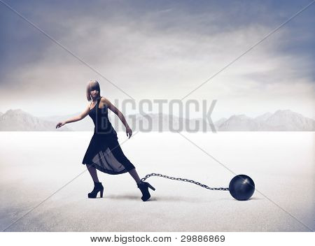 Young woman running with an iron ball tied to her ankle