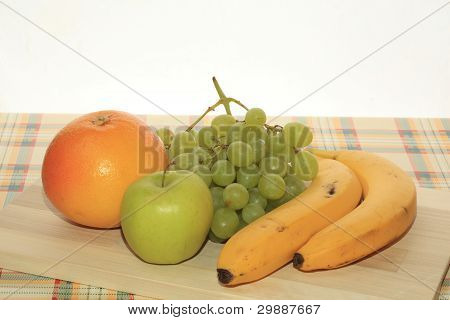 Fresh Green Grapes, Apple, Banana And Grapefruit On A Table