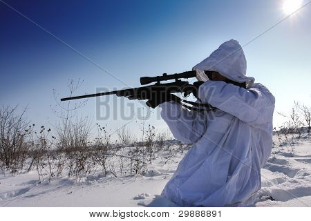 Hunter in white camouflage suit with a sniper rifle