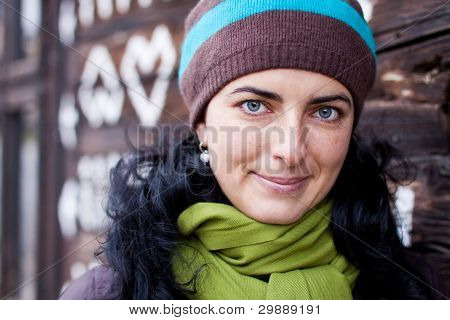 Woman leaning against wooden house.