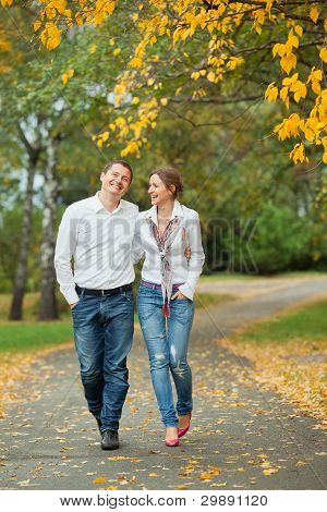 Romantic young beautiful couple on autumn walk