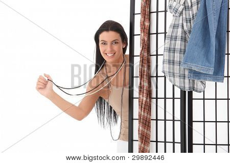 Happy young woman standing behind dressing panel, smiling, wearing necklace.?
