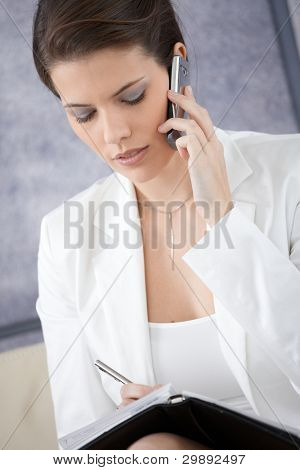 Businesswoman taking notes into personal organizer, concentrating on mobile phone call.?