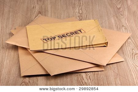 Envelopes with top secret stamp on wooden background