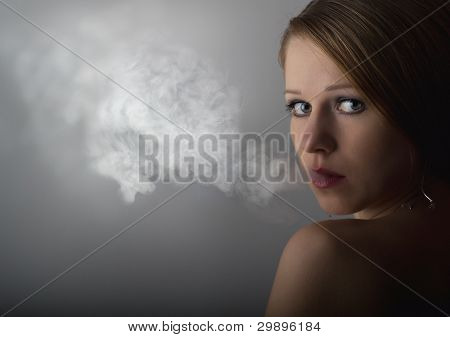 Beautiful Young Woman With Cigarette Smoke On A Dark Gray Background