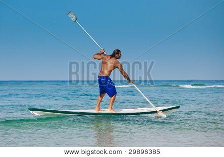 El chico con un remo en una tabla de surf.