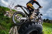 Enduro Bike Rider In Action. Obstacle Overcome On Mud And Grass Terrain. poster