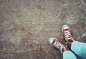 Photo of a red gumshoes over dirty sand background, cool teenagers shoes, urban youth lifestyle poster