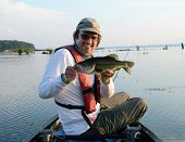 A Largemouth Bass Being Held By A Smiling Man In A Canoe In Mallows Bay On The Potomac River On A Ca poster