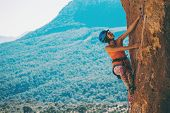 A Girl In A Helmet Climbs A Rock. Woman Overcomes Challenging Climbing Route On The Background Of Be poster