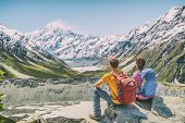 Backpackers couple hiking looking at Mount Cook view on mountains tramping in New Zealand. People hi poster