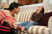 picture of tickle  - Mom tickles her daughter while on the couch - JPG