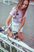Brunette Girl In The Summer In City. Locks Your Bike. Parking And Installation Of Cable And Lock Wit poster