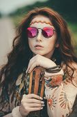 Close-up portrait of a beautiful hippie girl is standing with guitar on roadside outdoor. Contempora poster