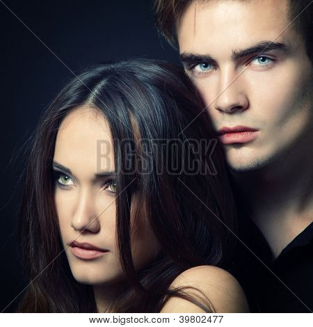 Sexy passion couple, beautiful young man and woman closeup, studio shot over black