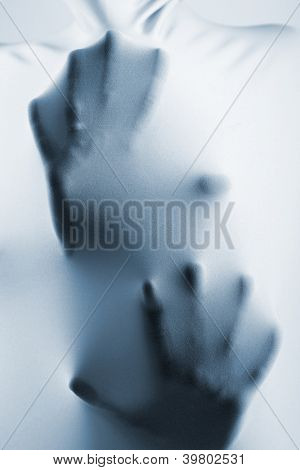 abstract hands, human arm inside fabric, studio shot toned blue