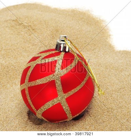 a red christmas ball on the sand, to symbolize christmas time in southern hemisphere