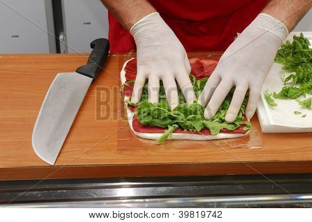Hand preparing rolled sandwich wrap.