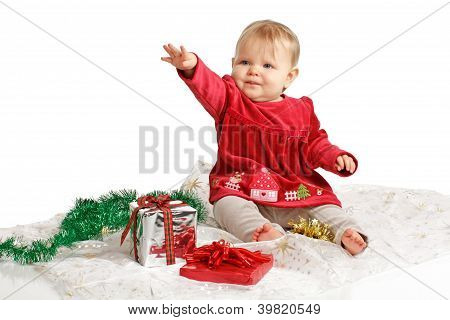 Baby In Red Velvet Dress Reaches Up With Holiday Gifts Nearby