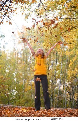 Beauty blond wirft Blätter im Herbst-park