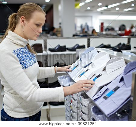 Woman is choosing shirt for man.