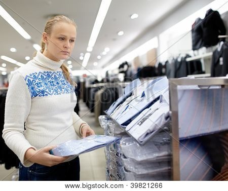 Woman is choosing shirt.